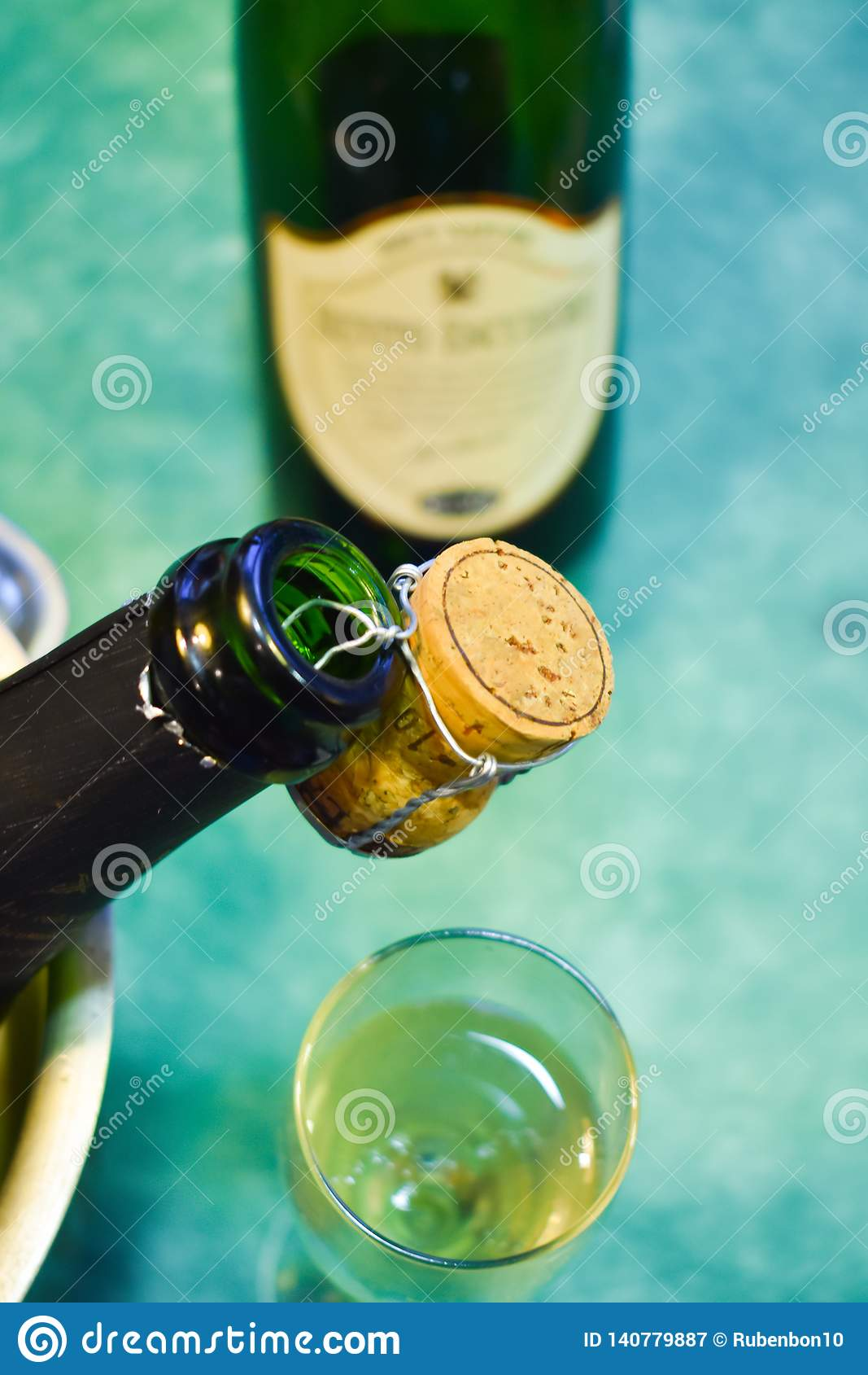 a champagne bottle in a cold bucket with ice and water, the cork holding from the mouth decorating the scene, a cup with sparking