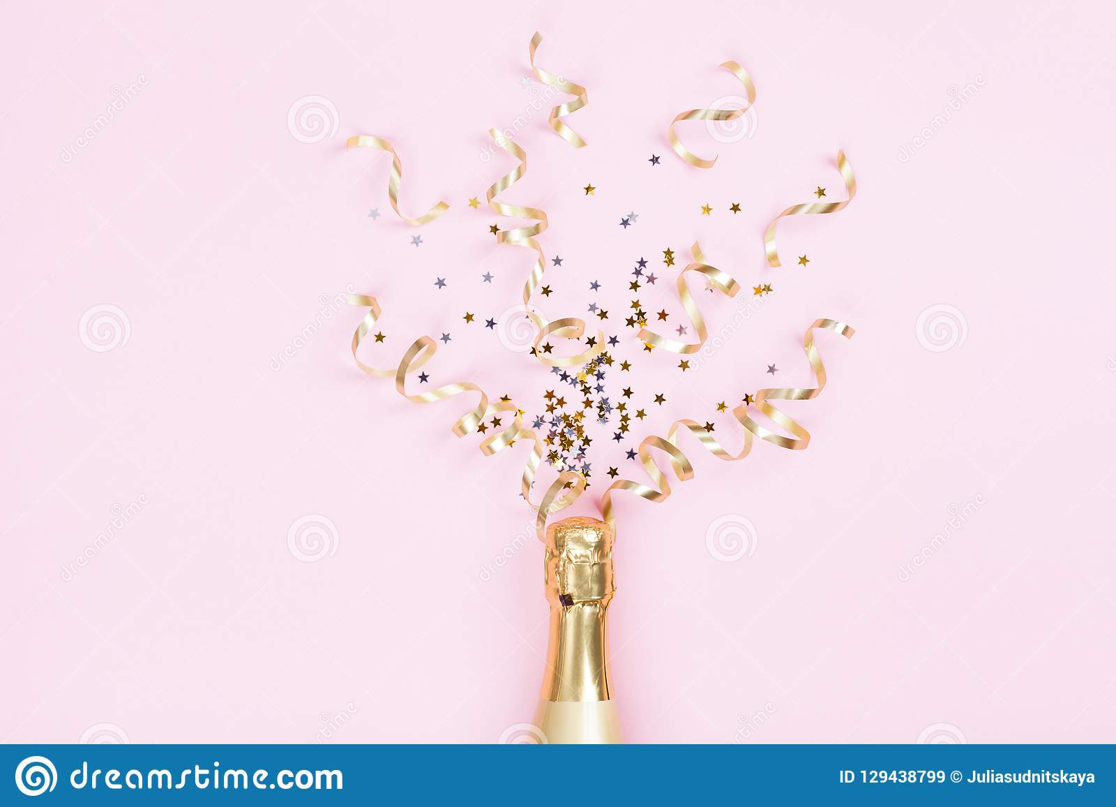 Champagne bottle with confetti stars and party streamers on pink background. Christmas, birthday or wedding concept. Flat lay.