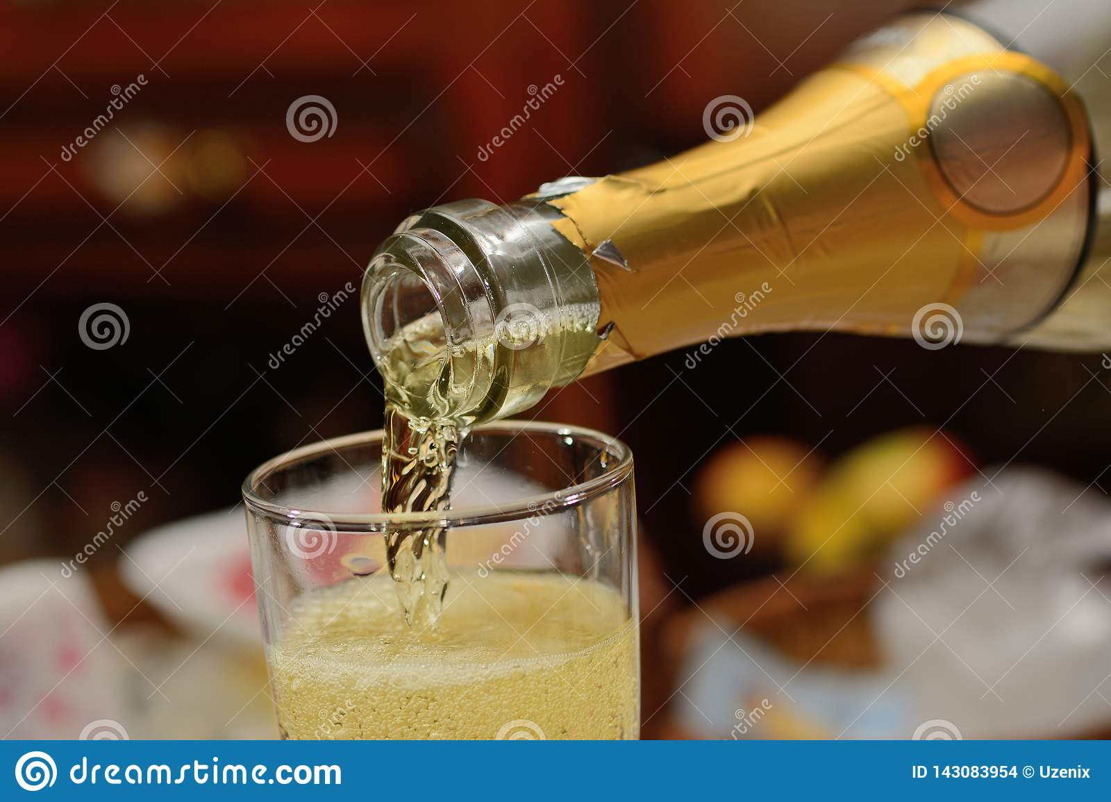 Champagne from a bottle is poured in a glass close up
