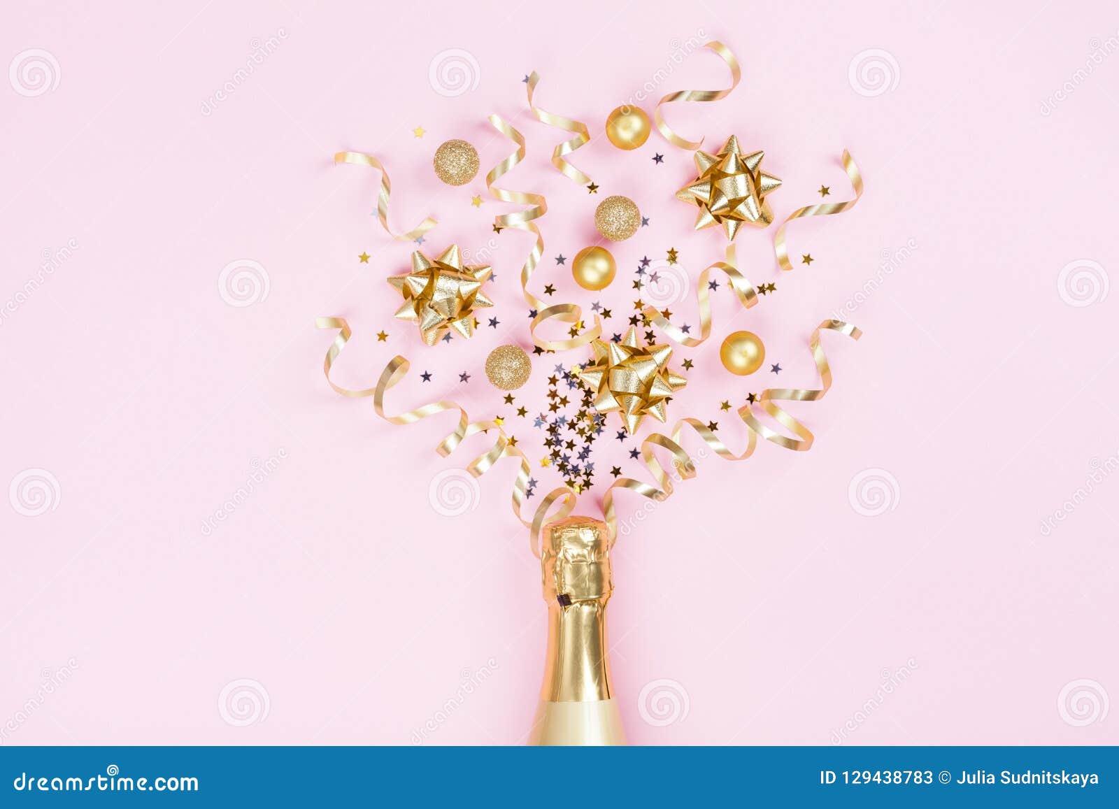 Champagne-fles met Kerstmisdecoratie van confettiensterren, gouden ballen en partijwimpels op roze achtergrond Vlak leg