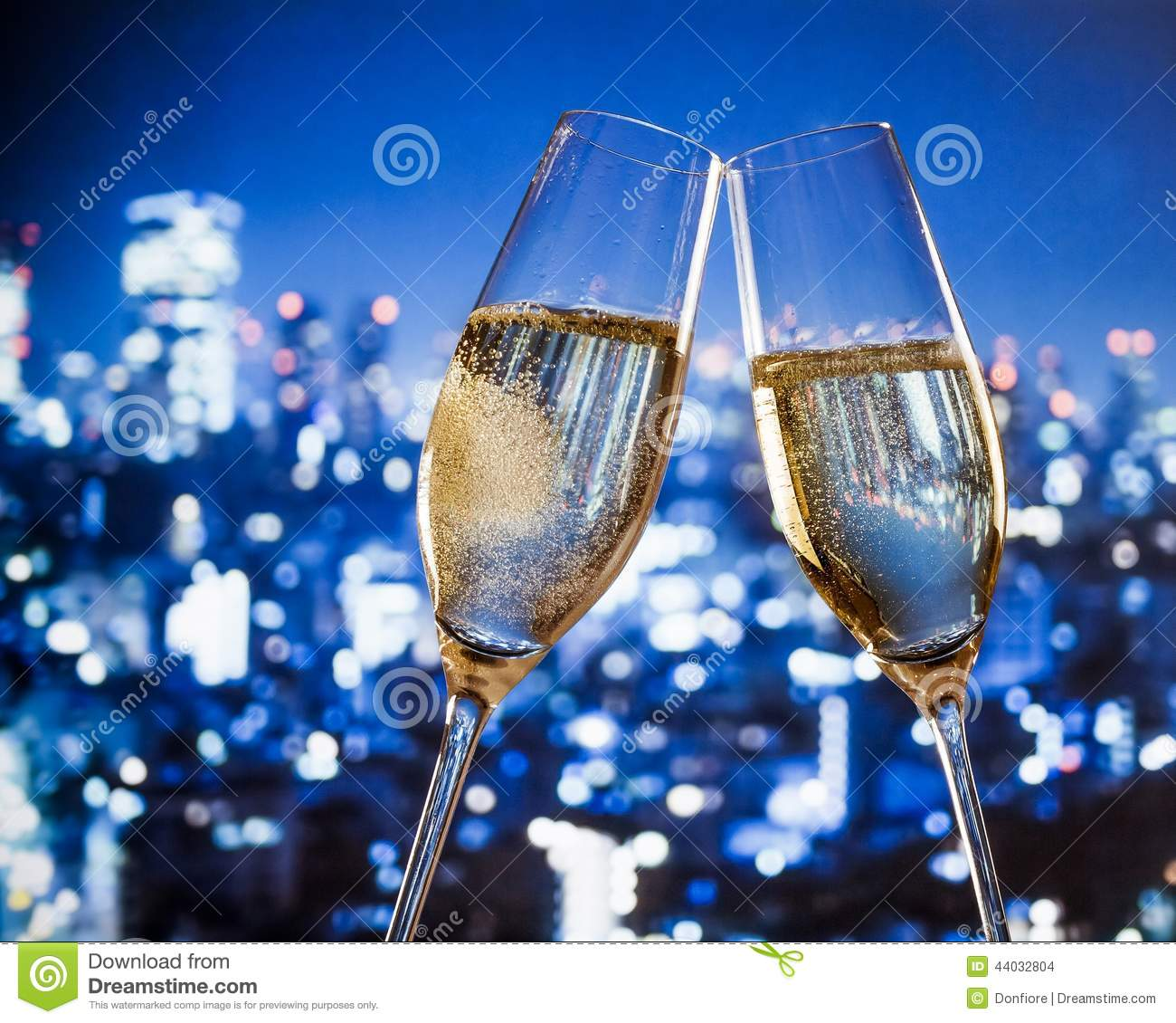 Champagne Flutes With Golden Bubbles On Blue City Night
