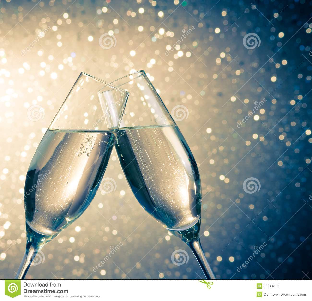 champagne flutes with golden bubbles on blue light bokeh background stock image