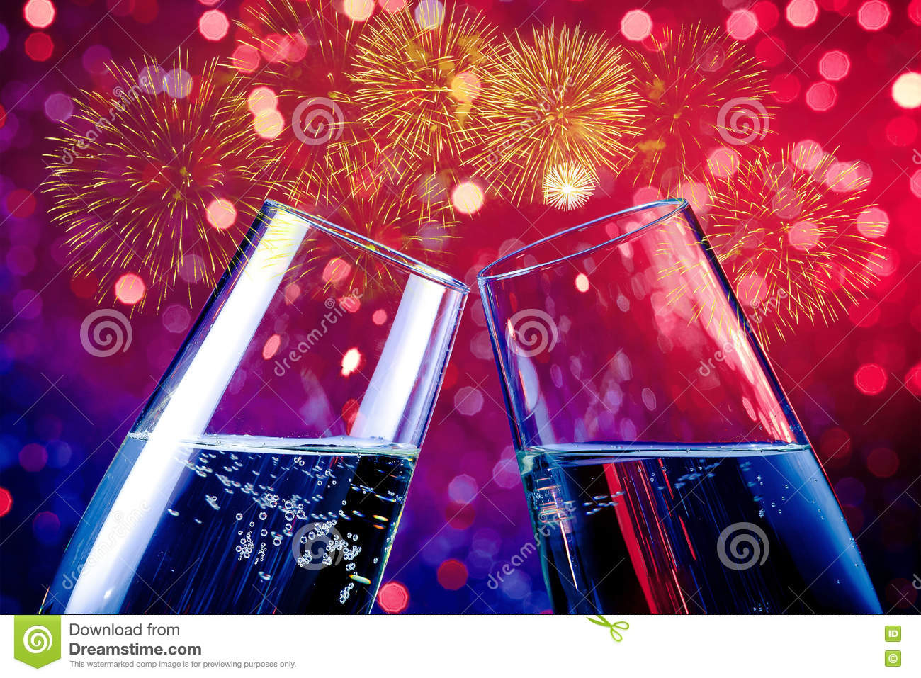 with space for text champagne flutes with golden bubbles on red and purple light bokeh and fireworks sparkle background