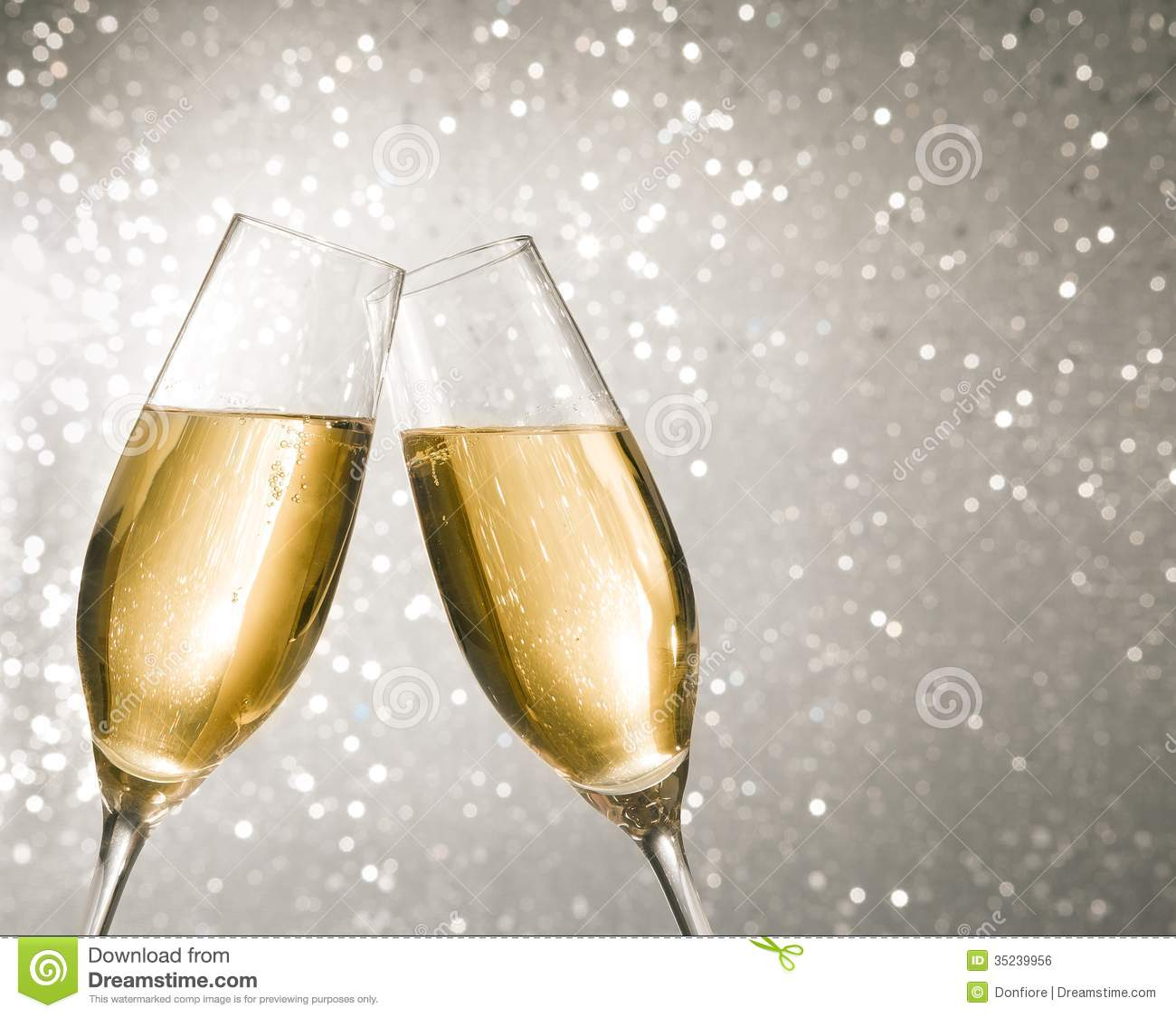Champagne flutes with golden bubbles make cheers on silver light bokeh ...