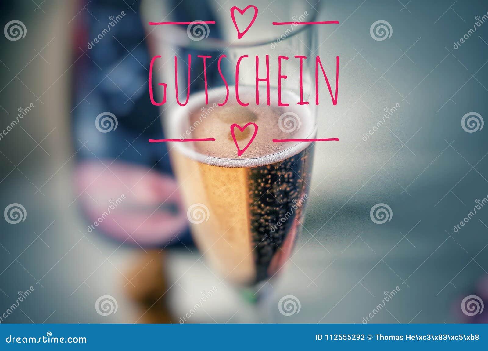 Champagne-glas met edele champagne en inschrijving in roze op Duitse Gutschein, in Engelse coupon, bon, giftkaart