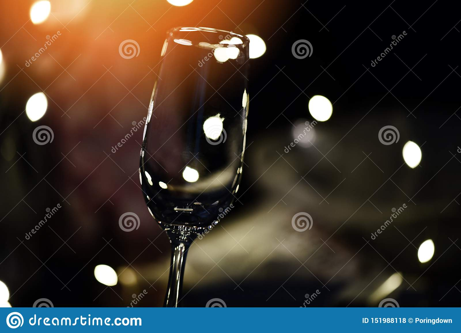 Champagne glass on table against blurred lights background - perspective of crystal clear wine glass for night party on the