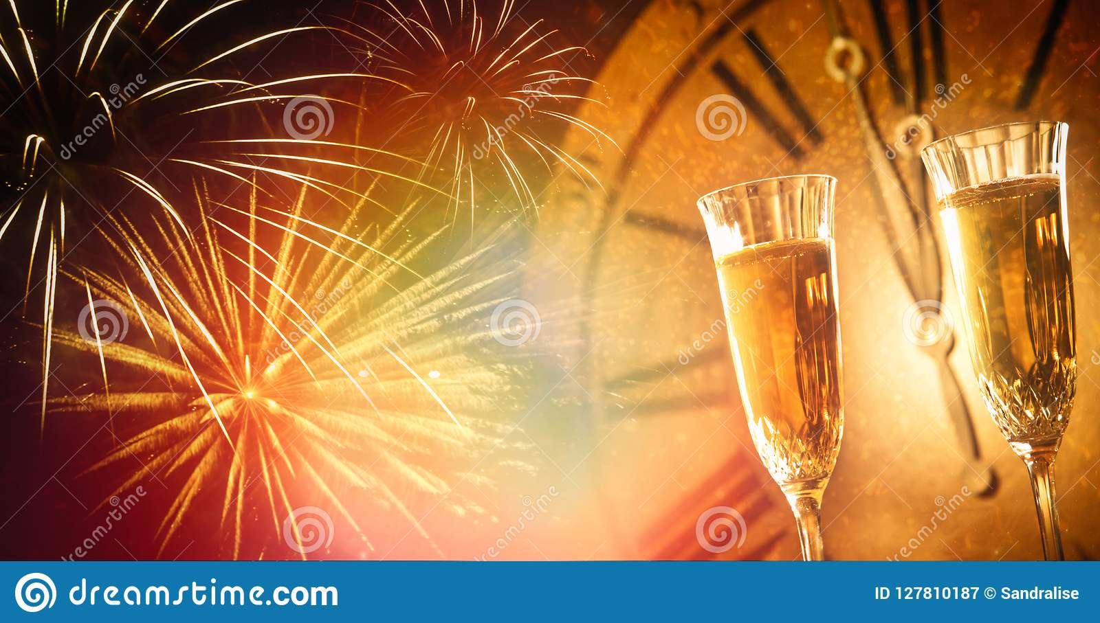 Champagne glasses against holiday lights and clock close at midnight