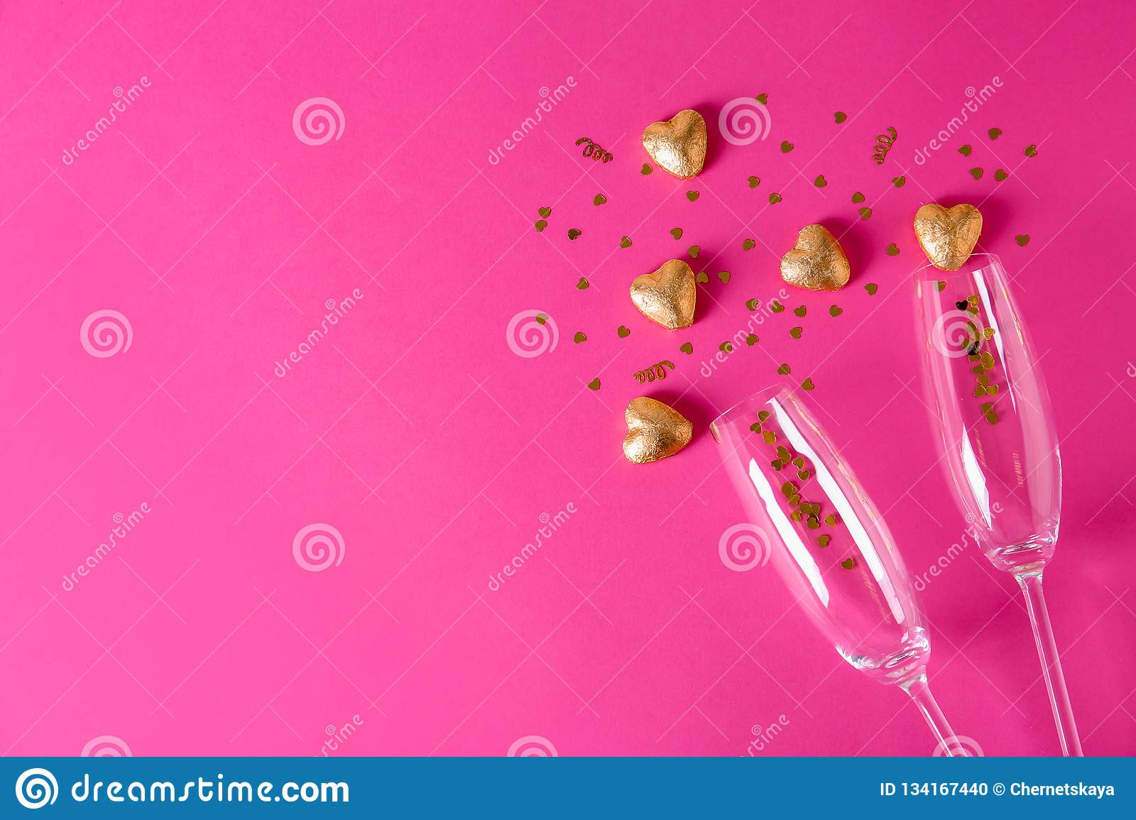 Champagne glasses and heart shaped candies in golden foil on color background