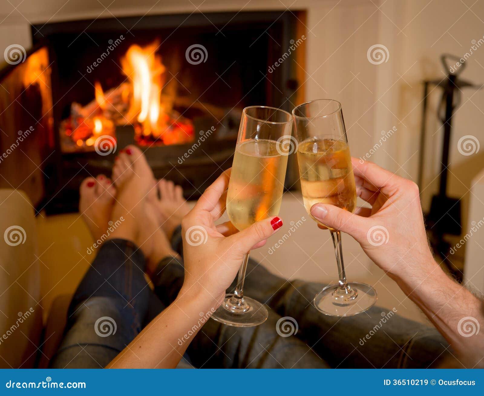 Champagne potable de couples devant un feu