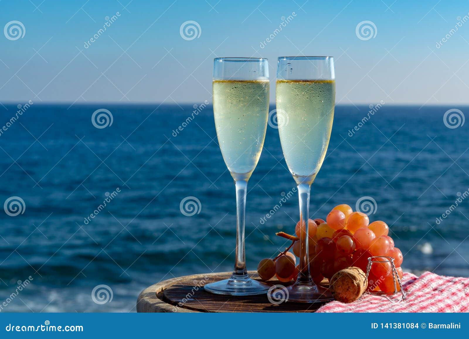 Champagne, prosecco ou cave servis avec du raisin rose en deux verres sur la terrasse extérieure avec la vue de mer