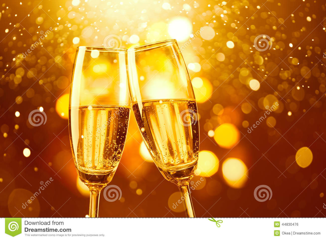 Two glasses of champagne toasting against gold bokeh background.