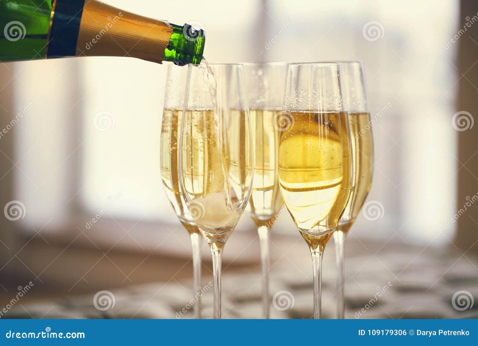 Champagneexponeringsglas och champagneflaska Champagne med den isolerade flygballonger och santa hatten