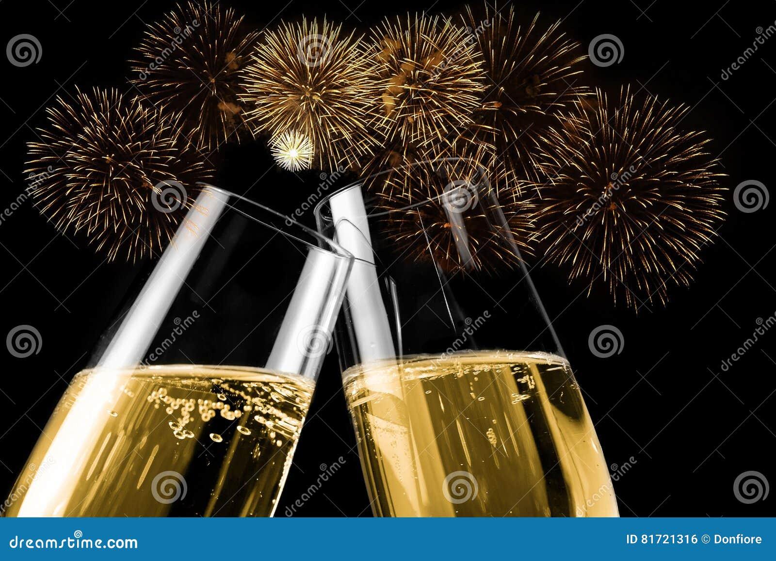 Champagneflöjter med guld- bubblor gör jubel med fyrverkerier att moussera och svärta bakgrund