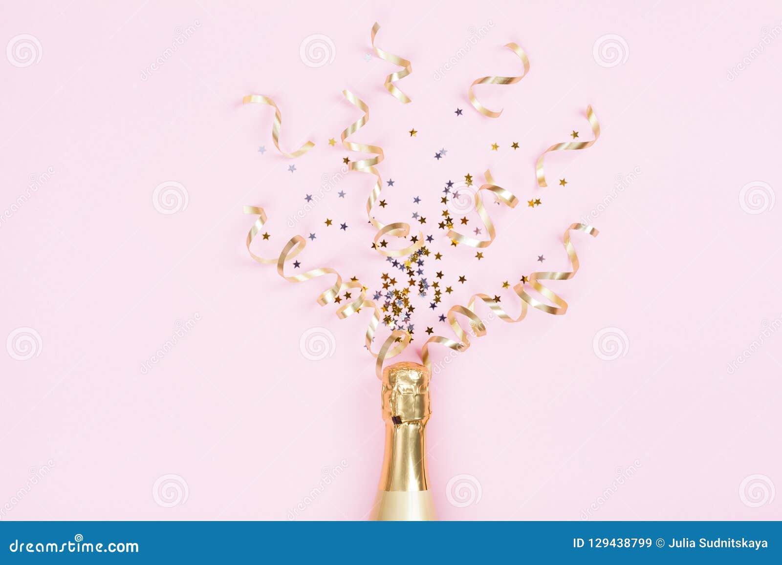 Champagneflaska med konfettistjärnor och partibanderoller på rosa bakgrund Jul, födelsedag eller bröllopbegrepp Lekmanna- lägenhe