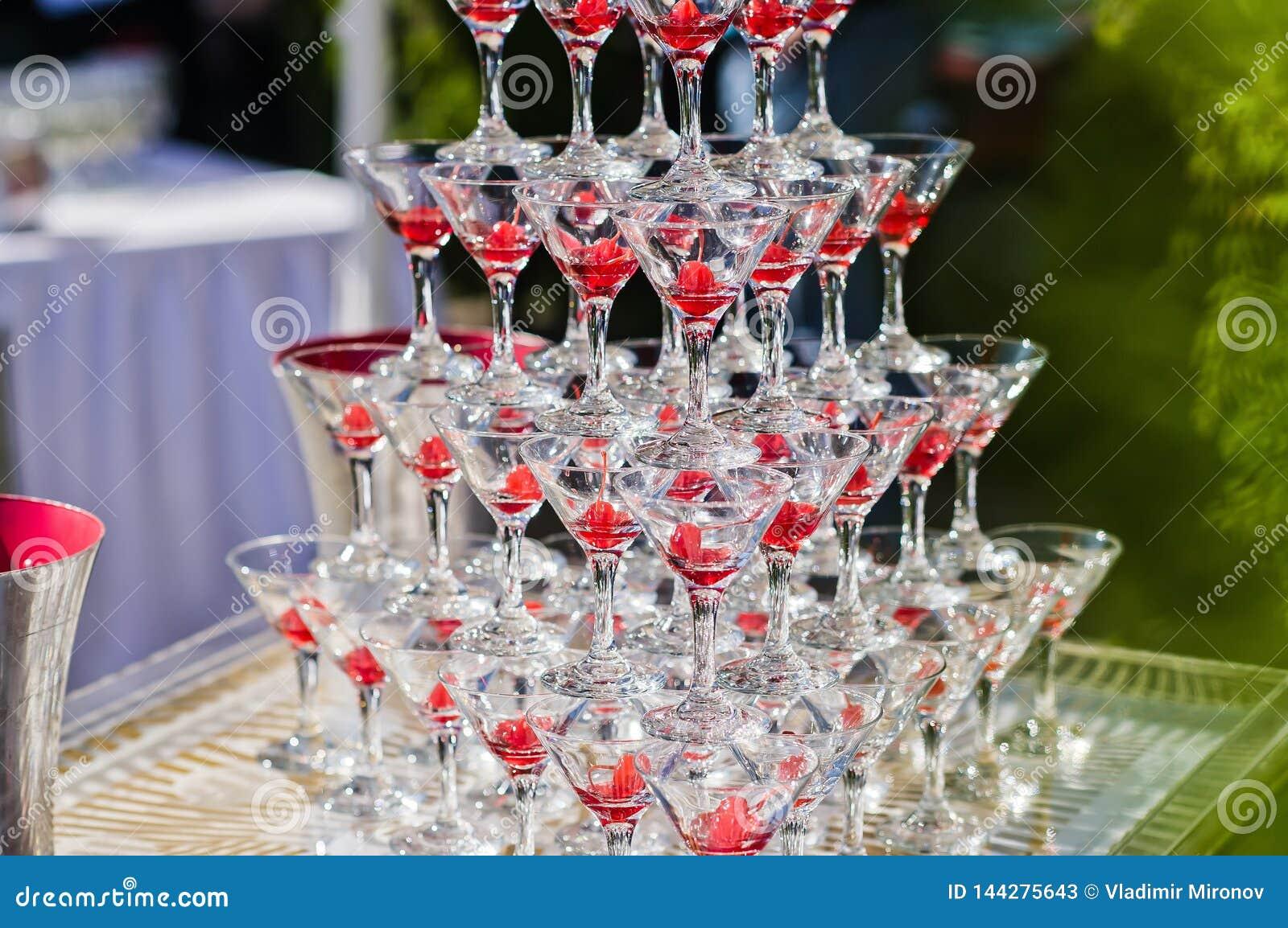 Champagneglidbana Pyramid eller springbrunn som göras av champagneexponeringsglas med körsbäret