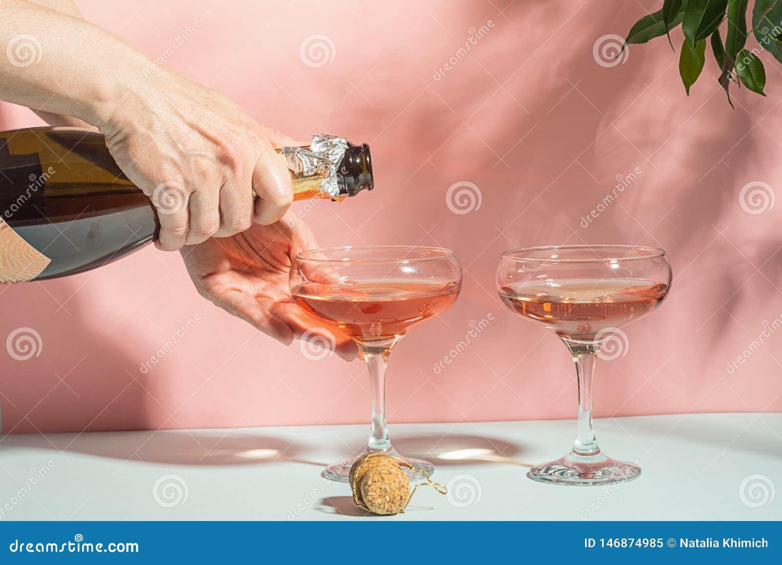 Champanhe de derramamento ou vinho da mão fêmea em vidros Luz solar brilhante do fundo delicado do rosa Minimalismo do espaço da