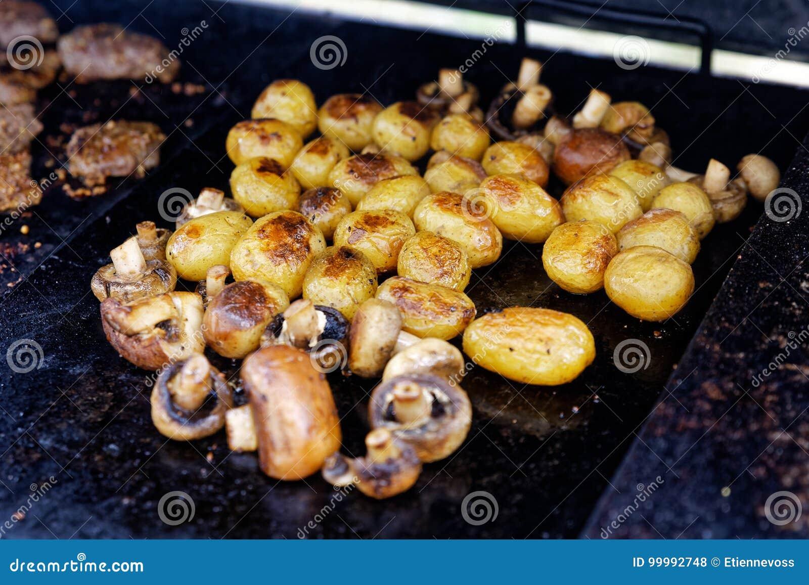 Champignons grillés et pommes de terre entières sur le gril extérieur