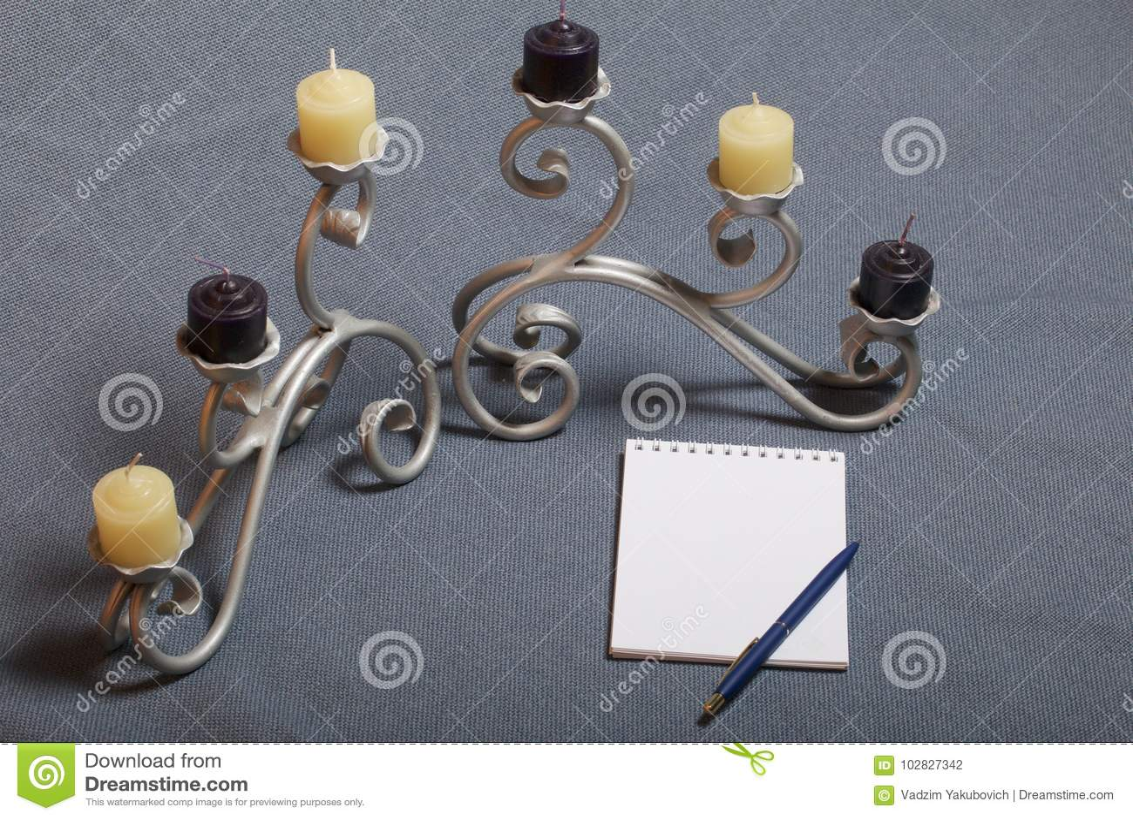 Chandelier forgé en métal avec des bougies Il y a un bloc-notes ouvert et un stylo