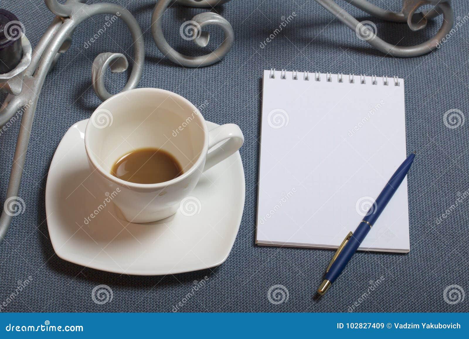 Chandelier forgé en métal avec des bougies Une tasse avec du café inapprouvé Il y a un bloc-notes ouvert et un stylo Feuilles d a