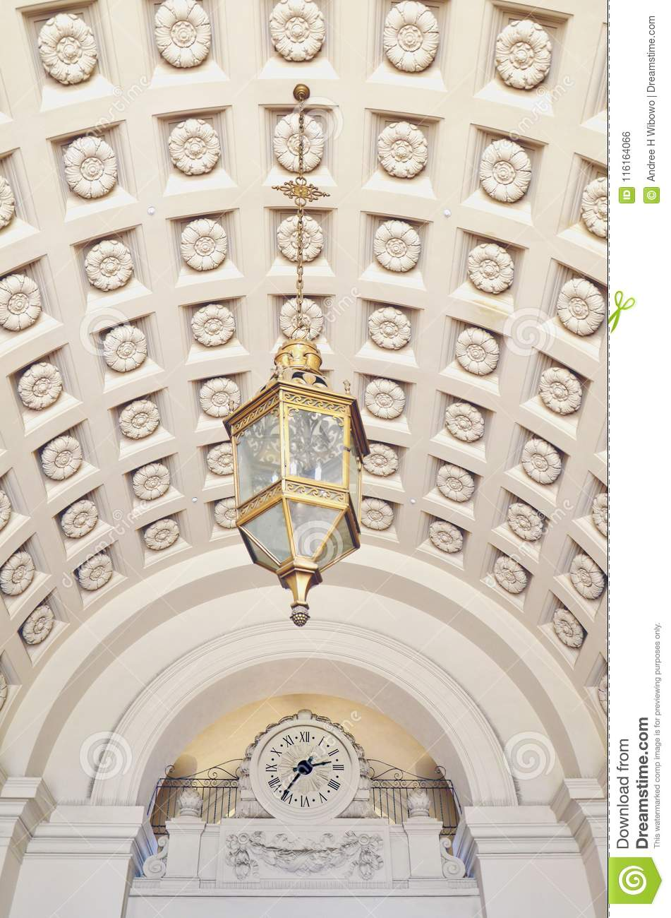 Chandelier Hanging from Ornamented Ceiling in front of a Clock