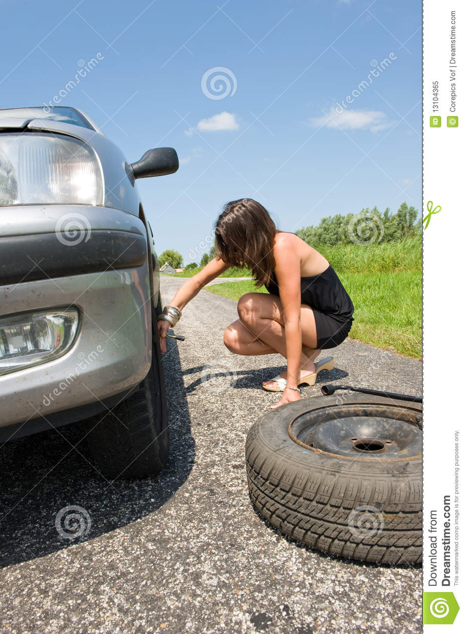 Young woman jacking up her car to change a flat tire with a spare one