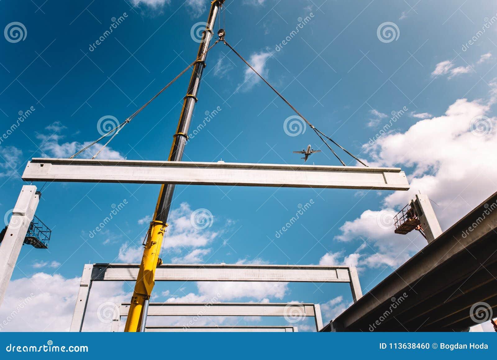 Chantier de construction industriel avec la grue à tour fonctionnant avec les faisceaux et les piliers préfabriqués