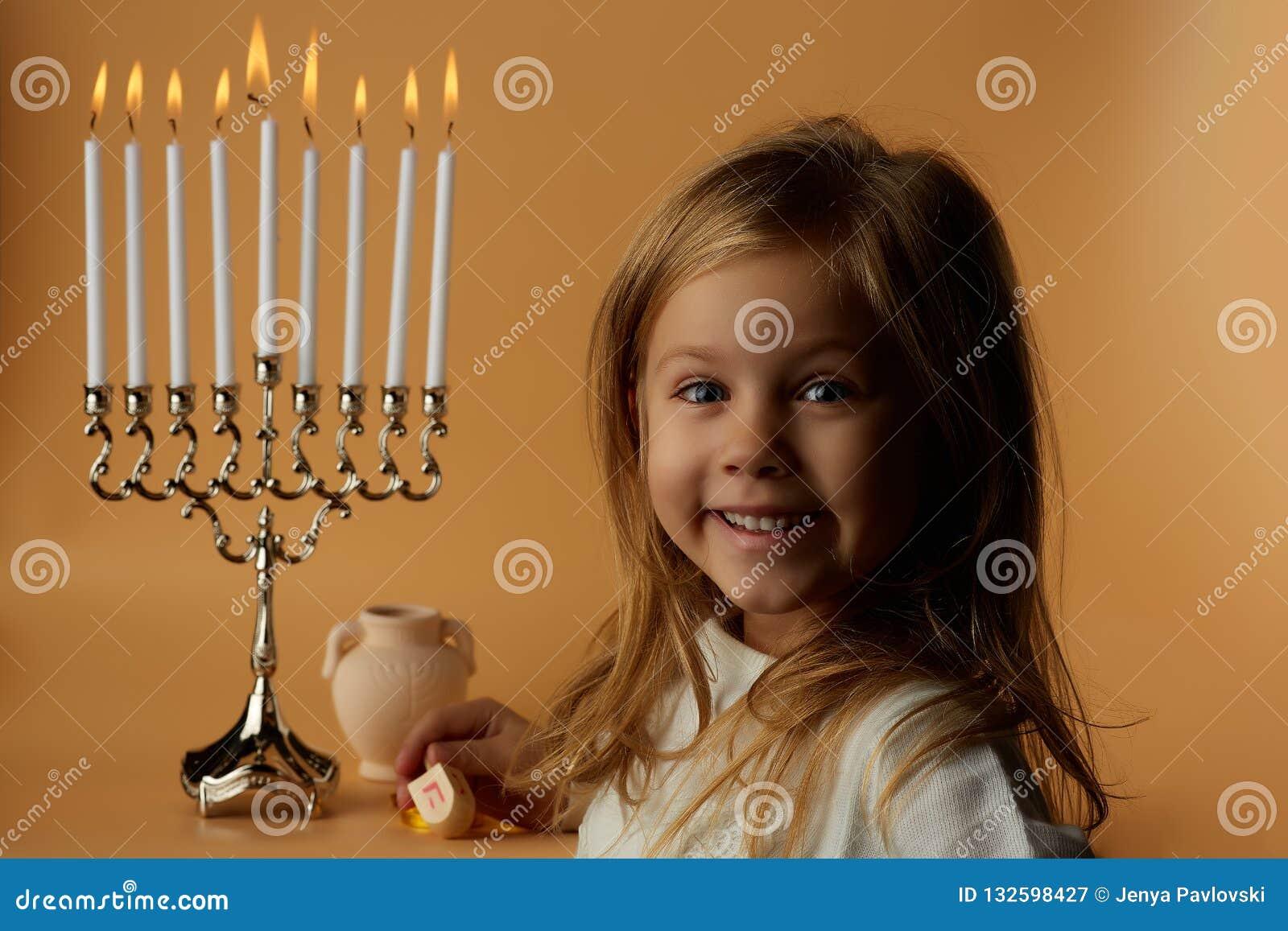 Chanukkah: Liten flicka på bakgrunden av stearinljusChanukkah