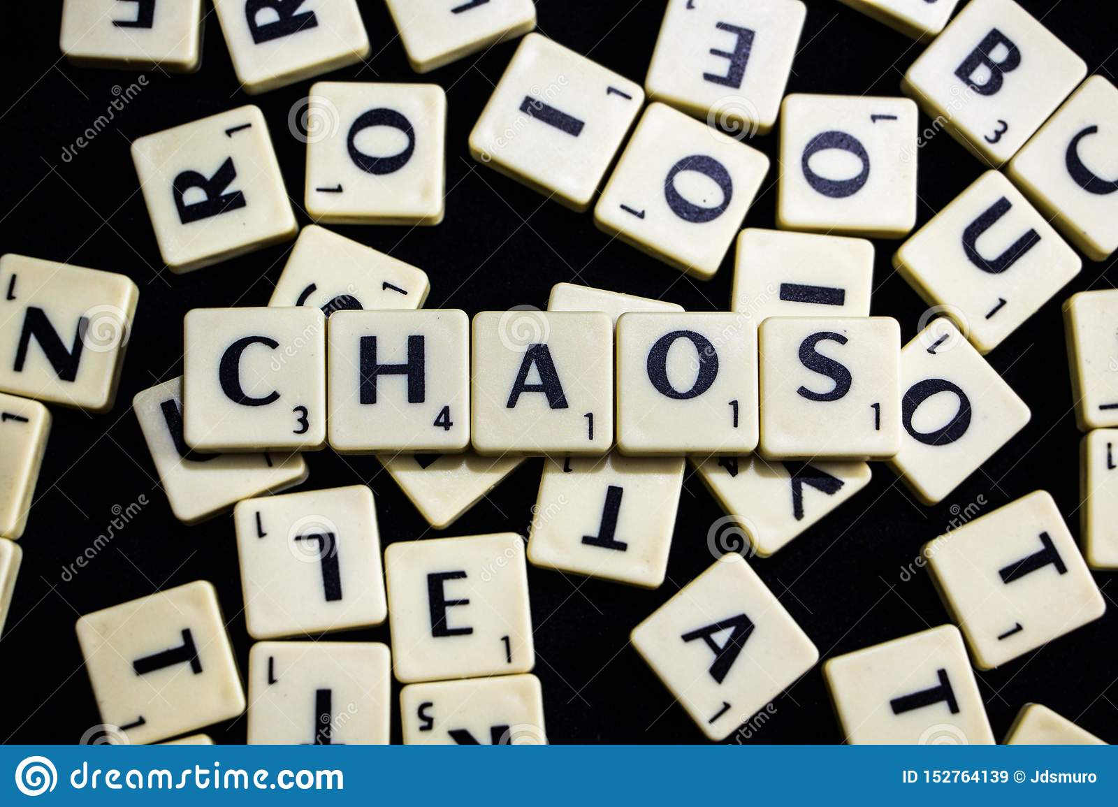 Chaos word spelled with scrabble letters in black background
