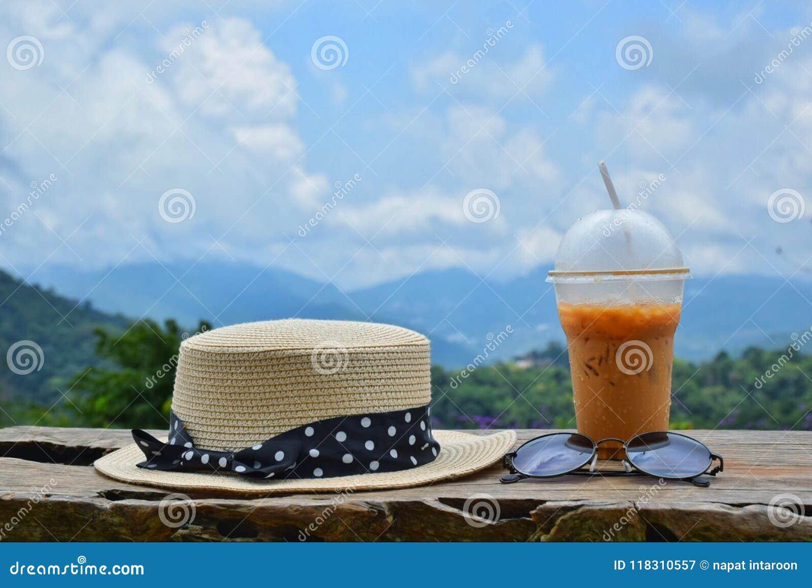 Chapéus, óculos de sol e chá gelado na natureza