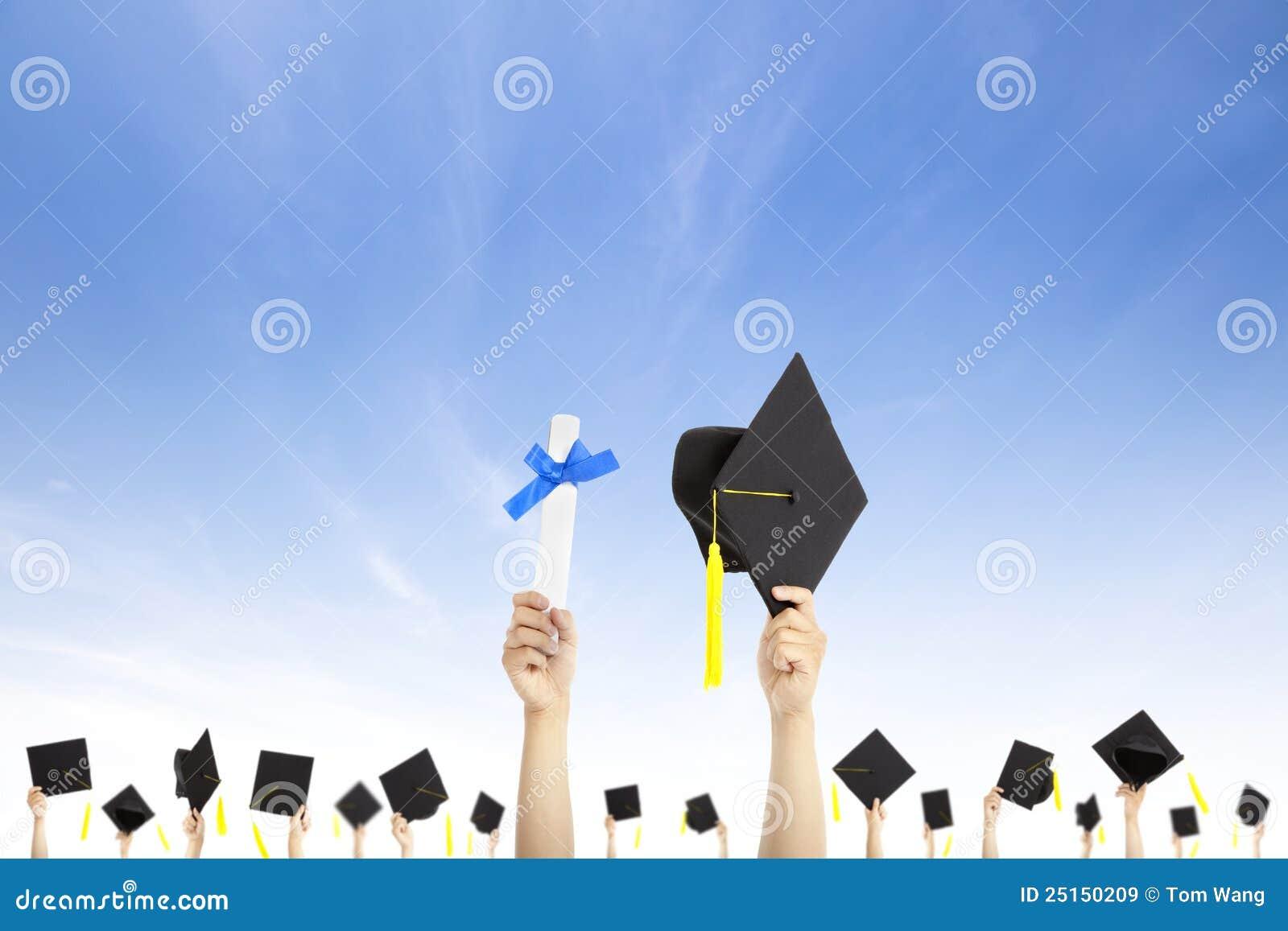 Chapéus e diploma da graduação da terra arrendada da mão