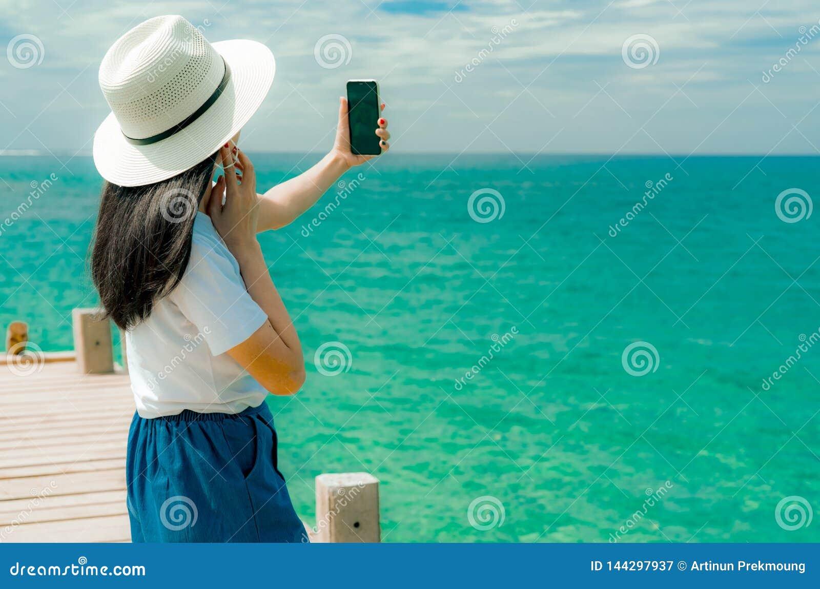 Chap?u asi?tico novo do desgaste de mulher no smartphone do uso do estilo ocasional que toma o selfie no cais F?rias de ver?o na