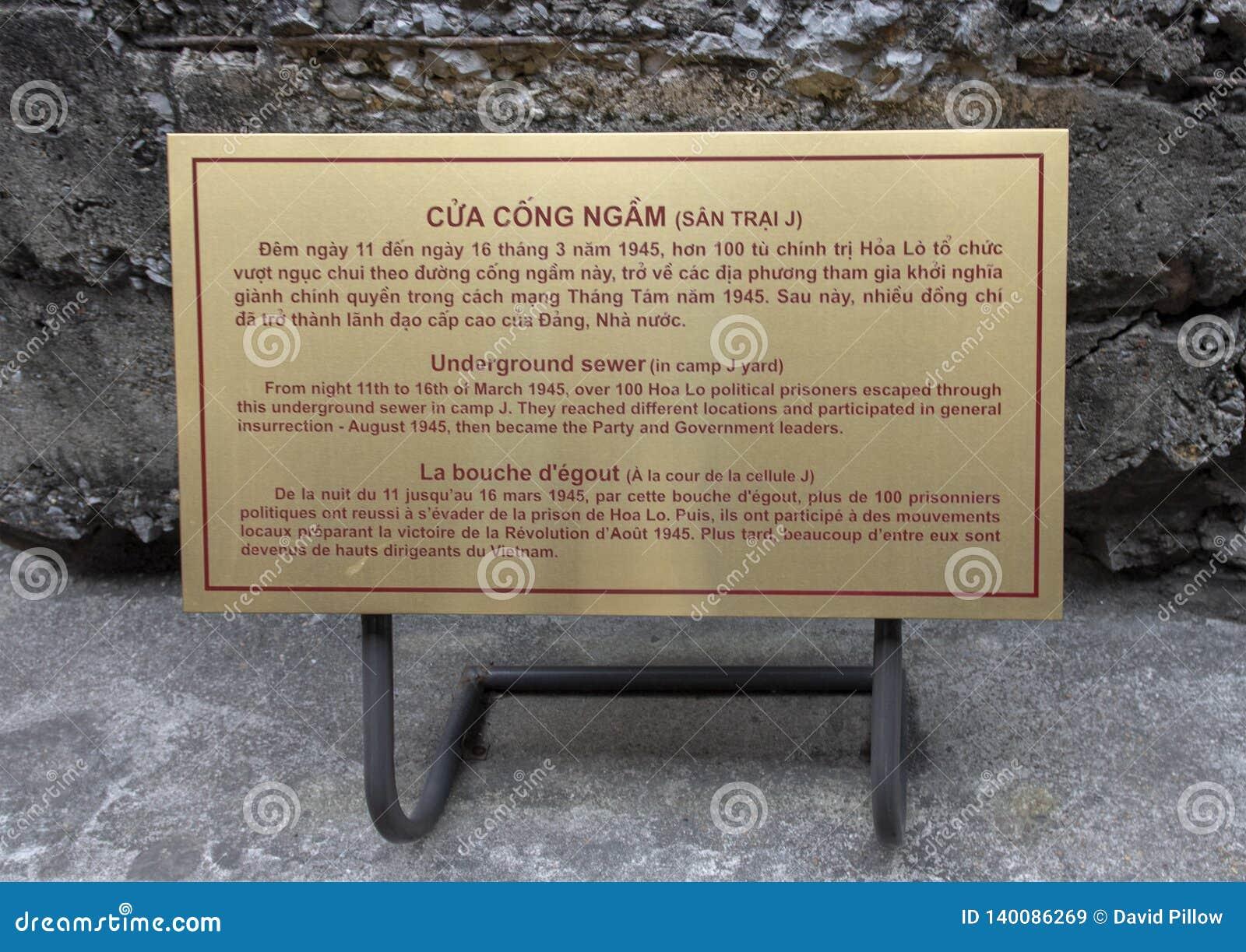 Chapa da informação para a via de fuga subterrânea do esgoto na exposição em Hao Lo Prison, Hanoi, Vietname