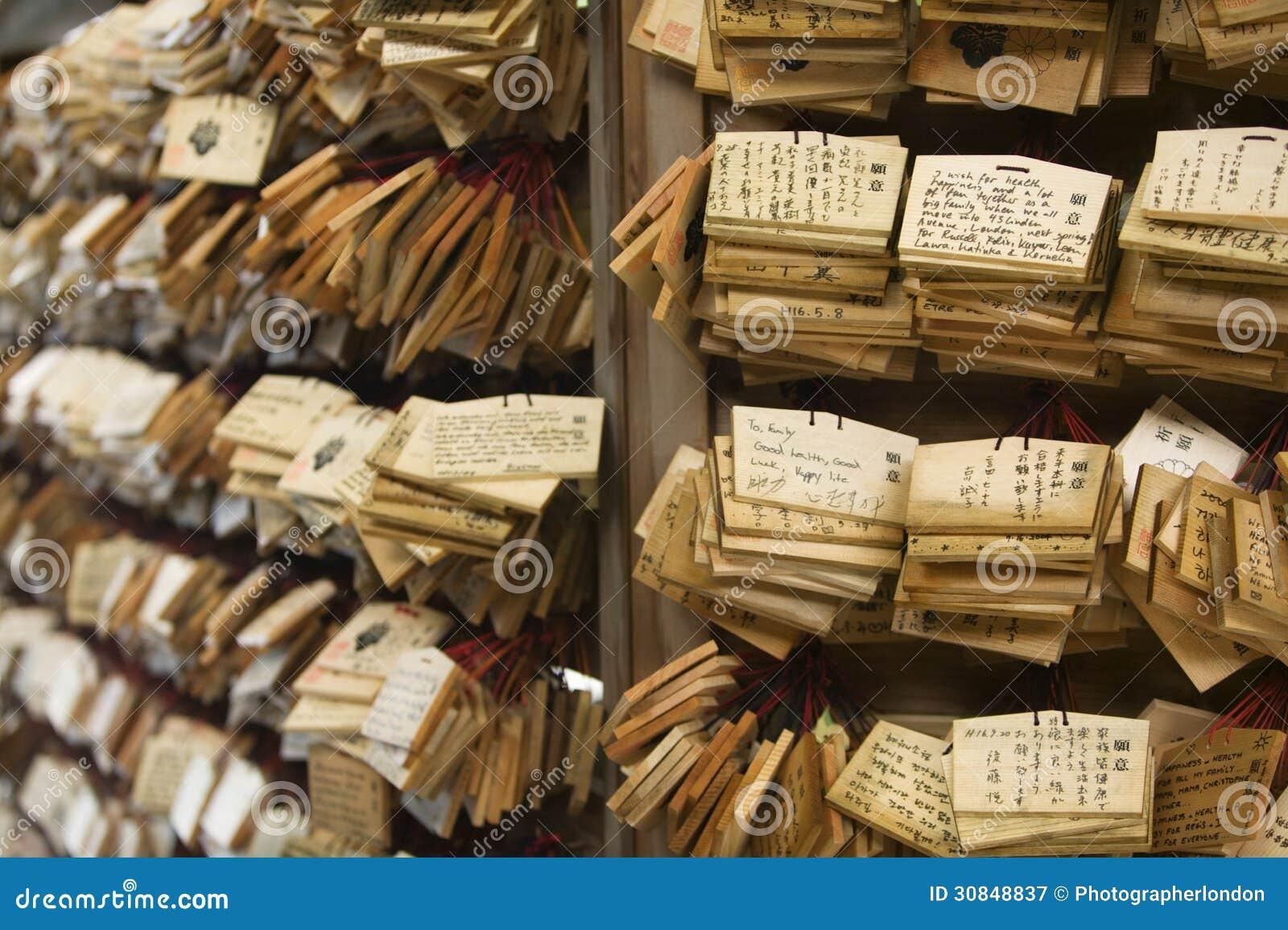 Chapas de madeira pequenas do santuário xintoísmo de Meiji-jingu do Tóquio de Japão com orações e desejos (Ema)