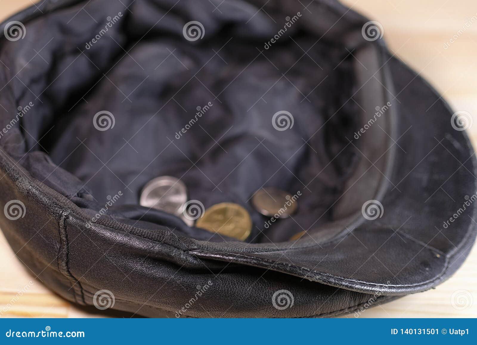 Chapeau avec quelques pièces de monnaie d aumône