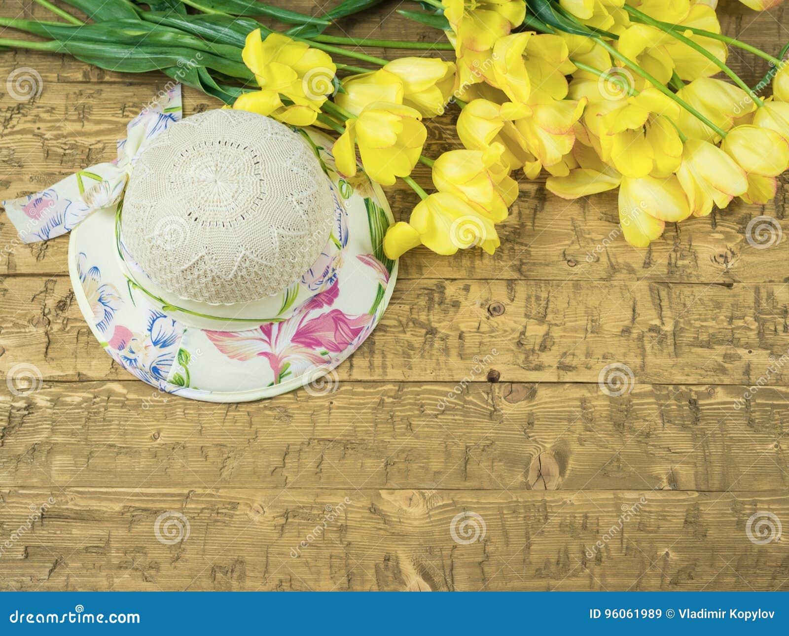 Chapeau avec un bouquet des tulipes jaunes sur une table en bois