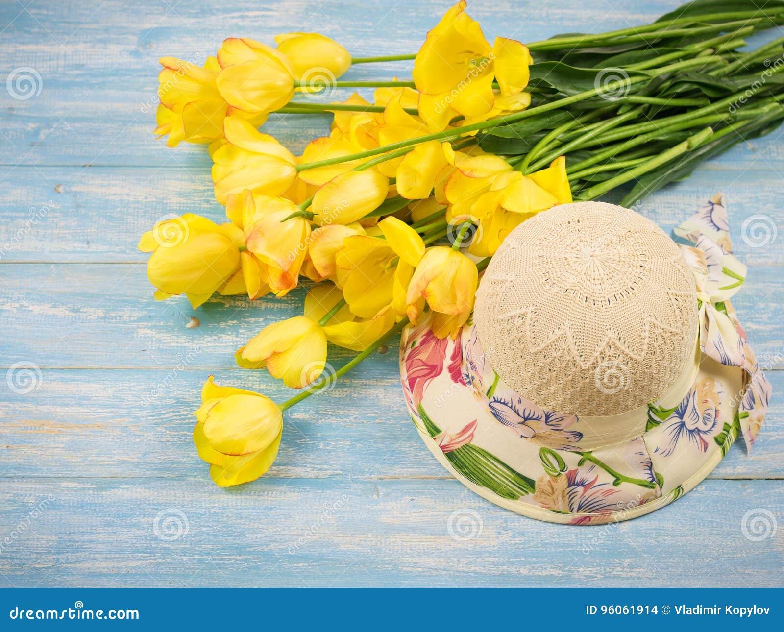 Chapeau avec un bouquet des tulipes sur une table en bois