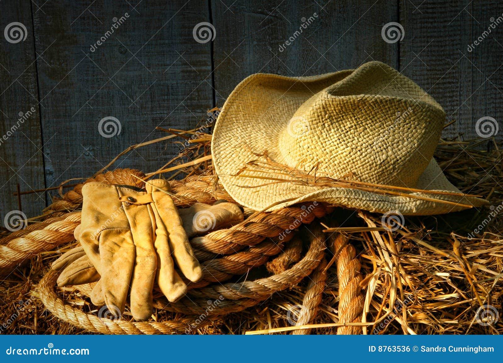 Chapeau de paille avec des gants sur une balle de foin