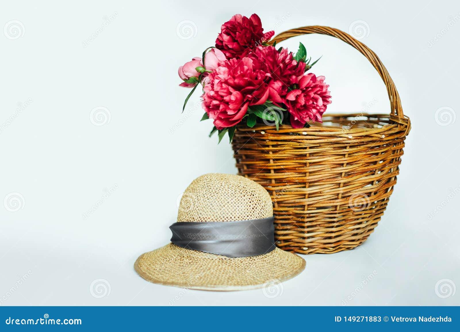 Chapeau de paille avec un bouquet des pivoines roses luxueuses