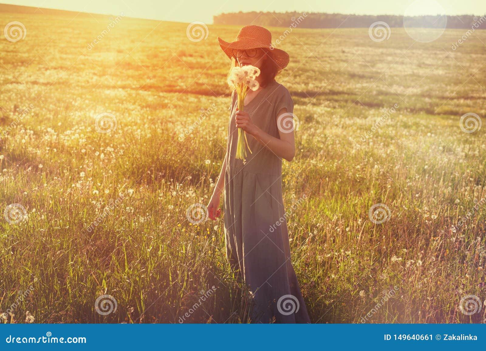 Chapeau de paille de port de femme et longue robe de toile appr?ciant la nature, tenant le bouquet de beaux pissenlits frais, jou