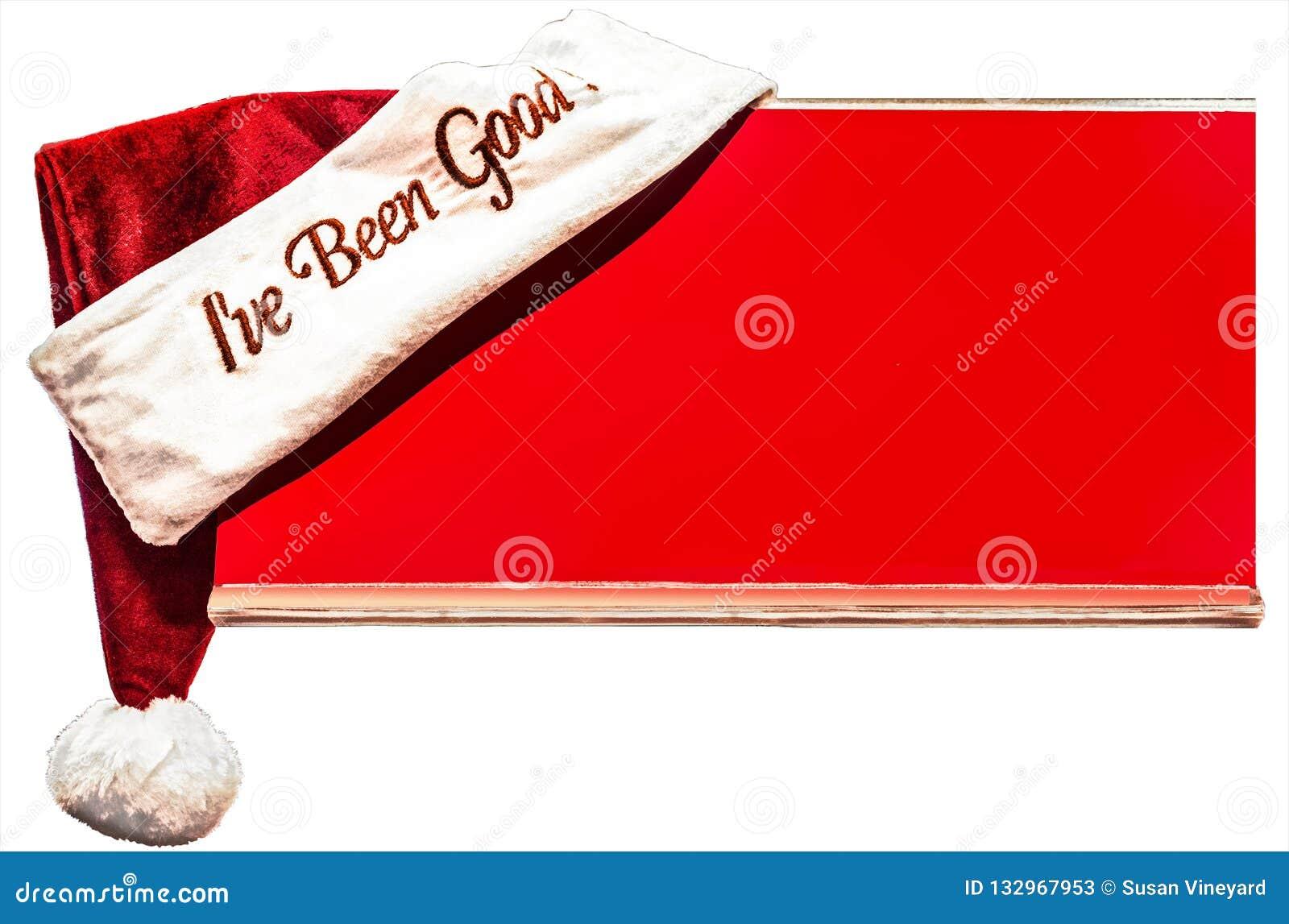 Chapeau de Santa de Noël avec des mots - j ai été bon - étés perché sur le coin du conseil rouge avec la pièce pour la copie d is