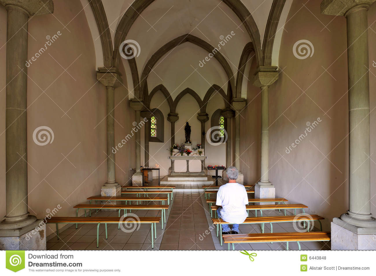 Inside a small chapel with a single worshipper sitting on a bench.