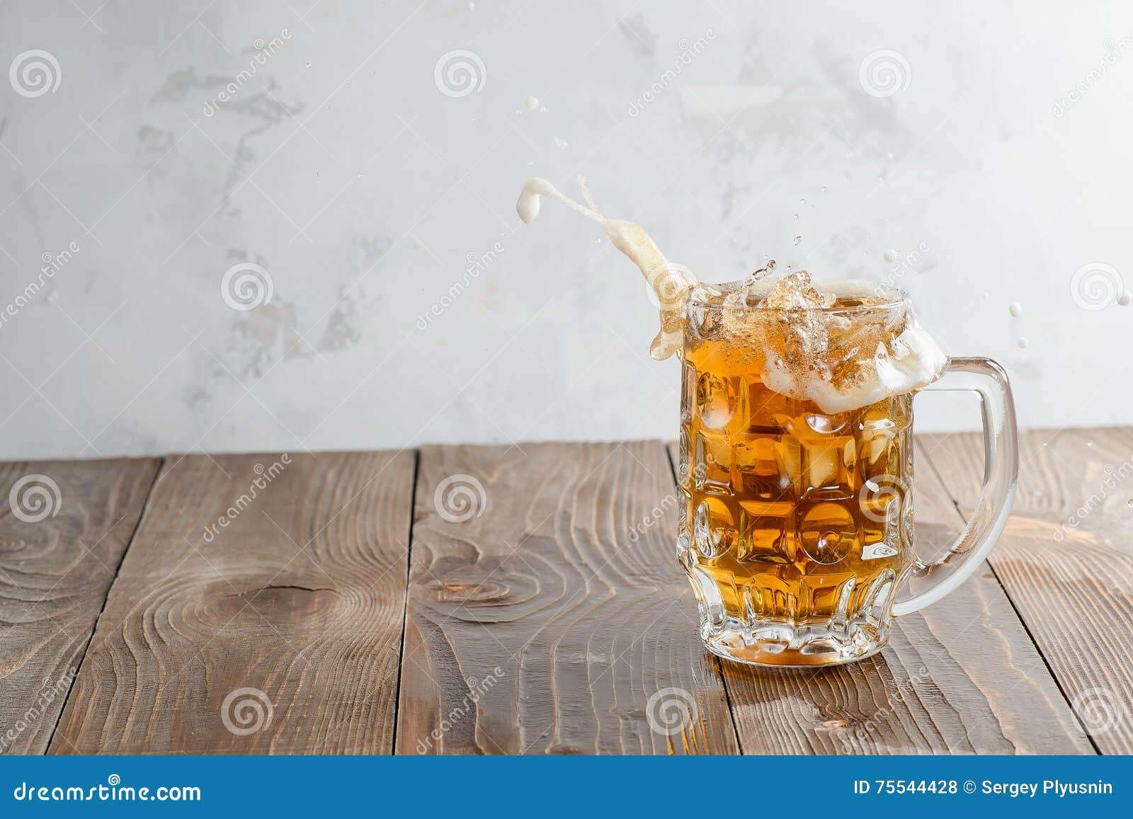 Chapoteo de la cerveza en vidrio en un fondo de madera