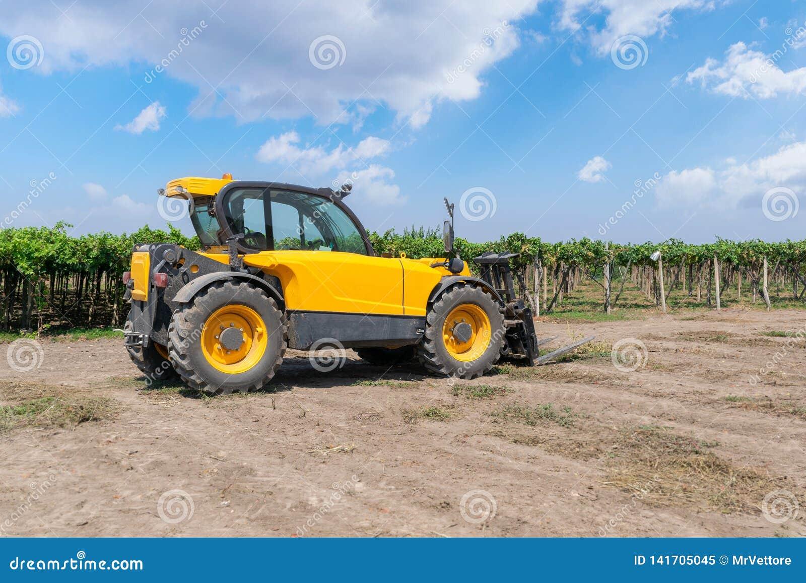 Chargeur de chariot élévateur de couleur jaune dans un domaine sur un fond de vignoble