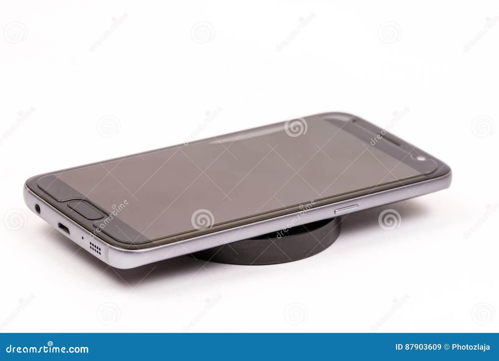 Chargeur mobile noir sans fil avec le téléphone portable d isolement au-dessus du fond blanc