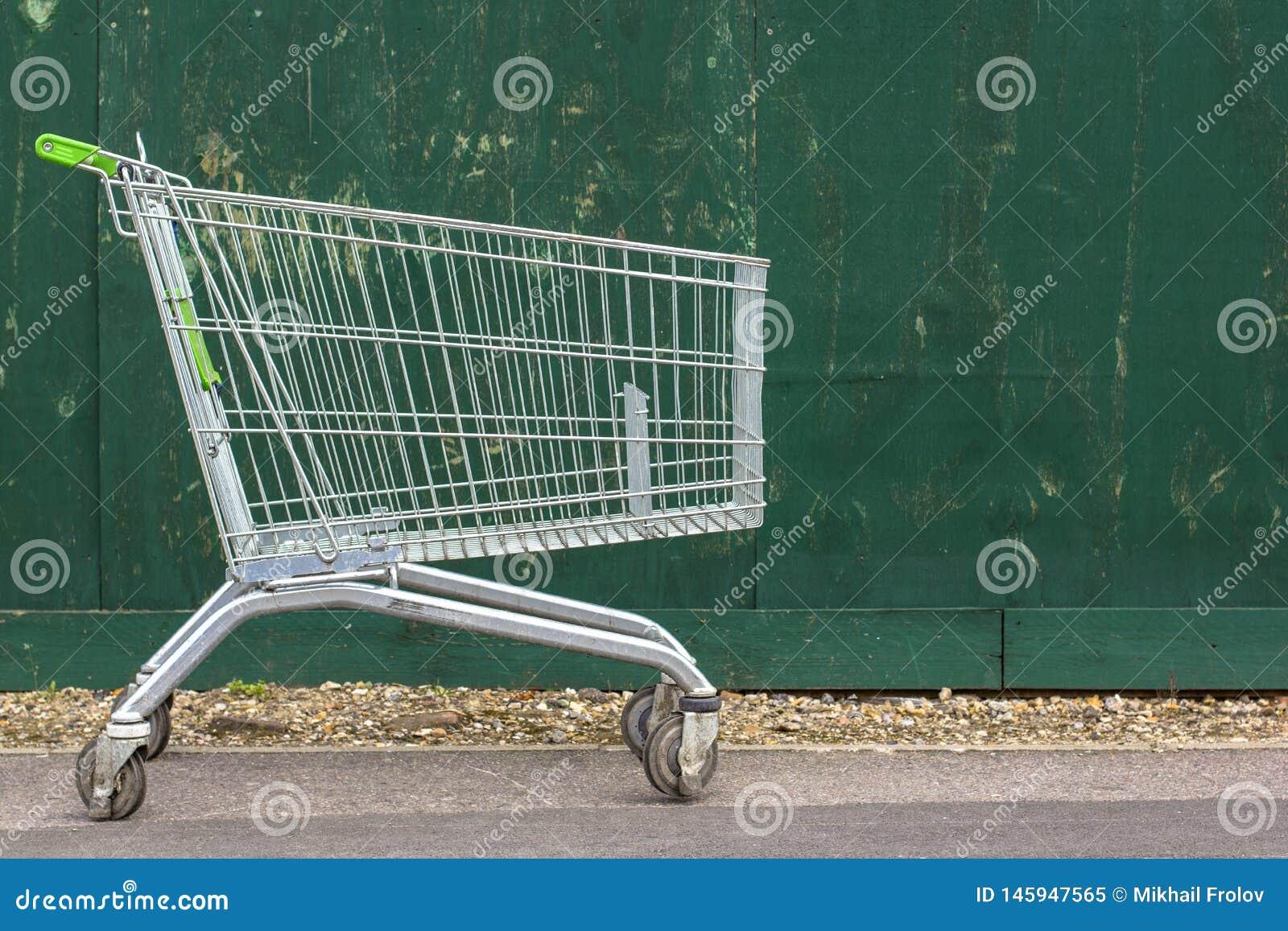Chariot à supermarché sur le fond d une barrière verte Chariot de supermarché sur le trottoir