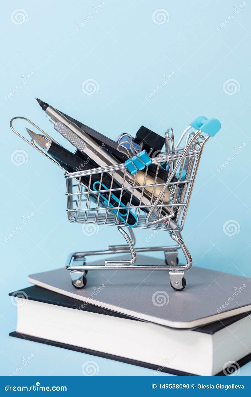 Chariot avec différents approvisionnements avec des livres sur le fond bleu ?ducation, de nouveau ? l ?cole, faisant des emplette