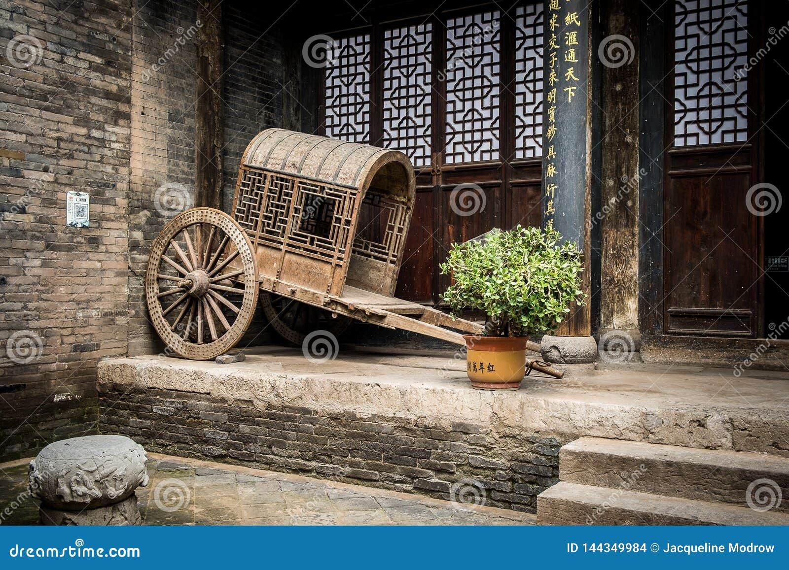 Chariot chinois antique vide se reposant contre un mur de briques