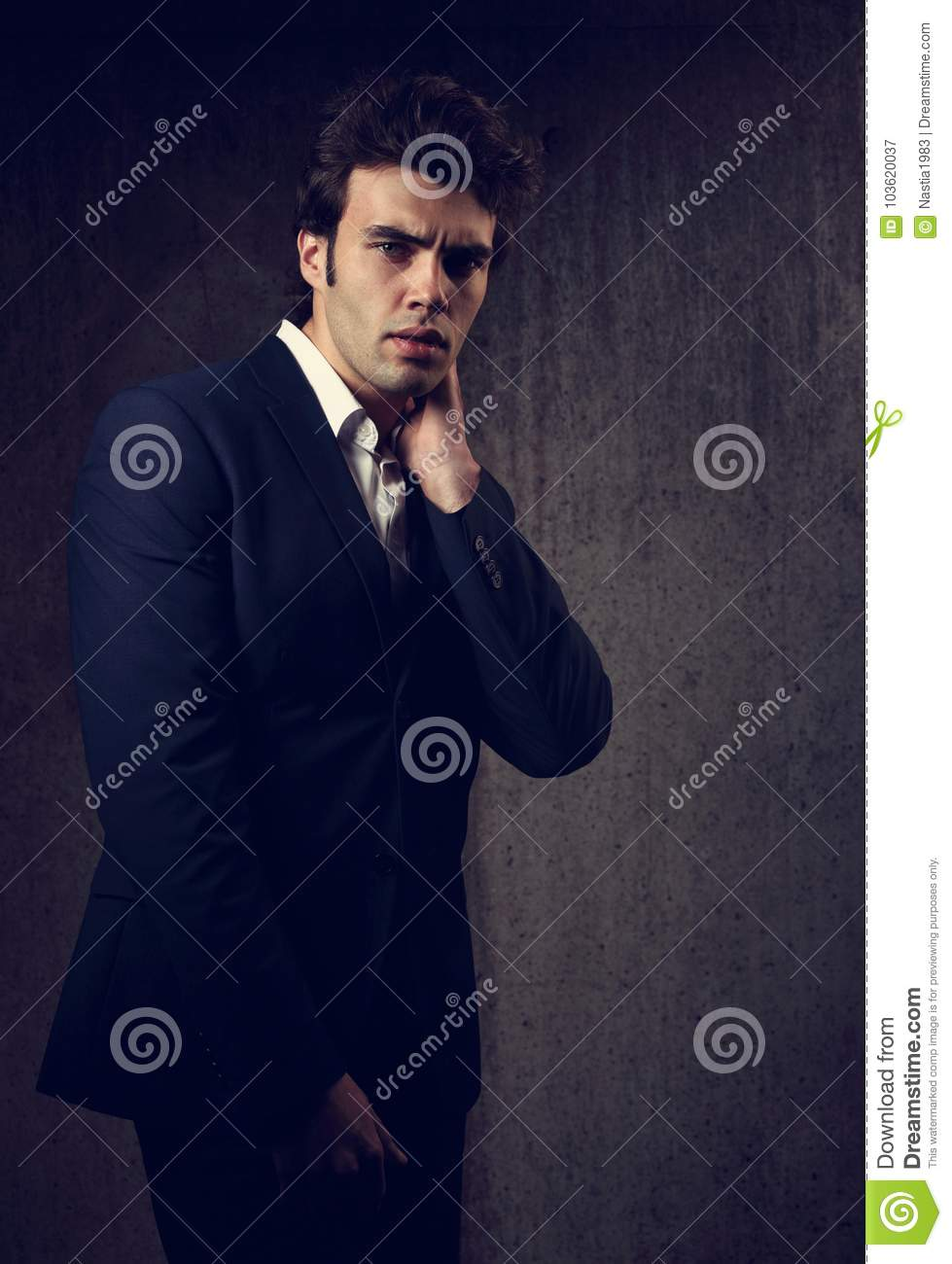00c6a240 Charismatic handsome male model posing in blue fashion suit and white style  shirt looking on dark shadow background.