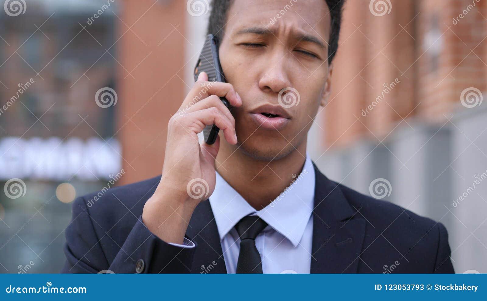 Charla del teléfono, hombre de negocios africano Attending Call