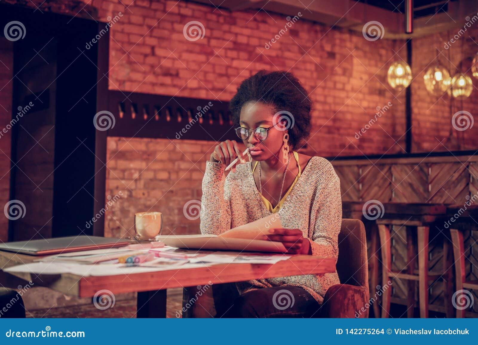 Charma Afro--amerikan den kvinnliga kontrollerande sketchbooken, medan sitta med kaffe